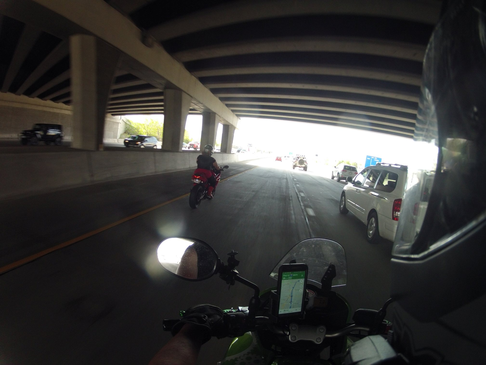 Pictured is a rider astride a motorcycle, helmet visible in the right foreground. Another rider appears two car lengths ahead on the left. They are under a shaded freeway overpass. In the cockpit of the bike a cell phone is visible, displaying GPS navigation with a blue highlighted route.