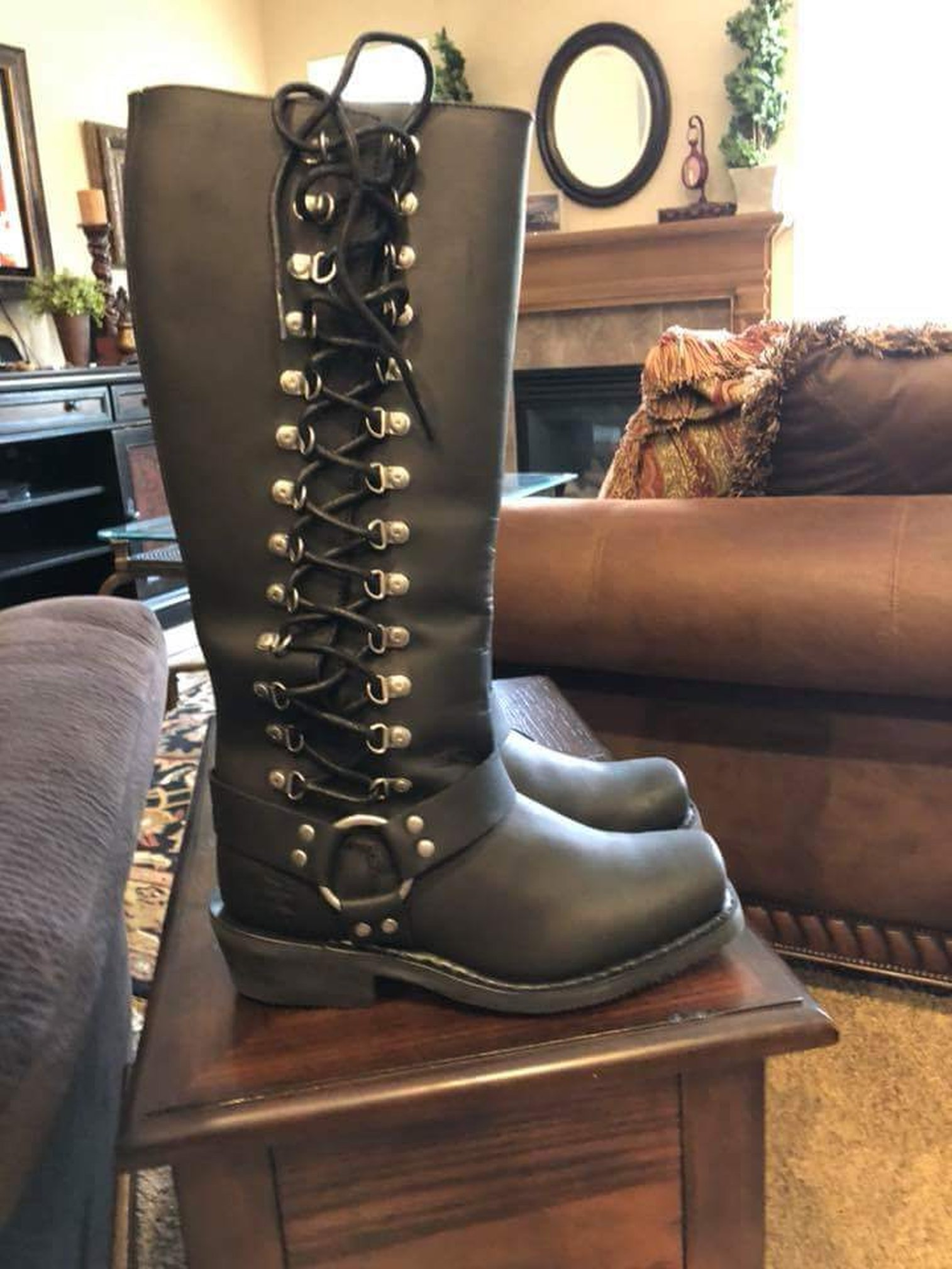Especially long Harley-Davidson brand boots with a thick sole. Laces run up the outside of the leg from ankle to calf, through heavy duty D rings. A leather strap at the ankle locates to a heavy silver ring on the outside ankle..