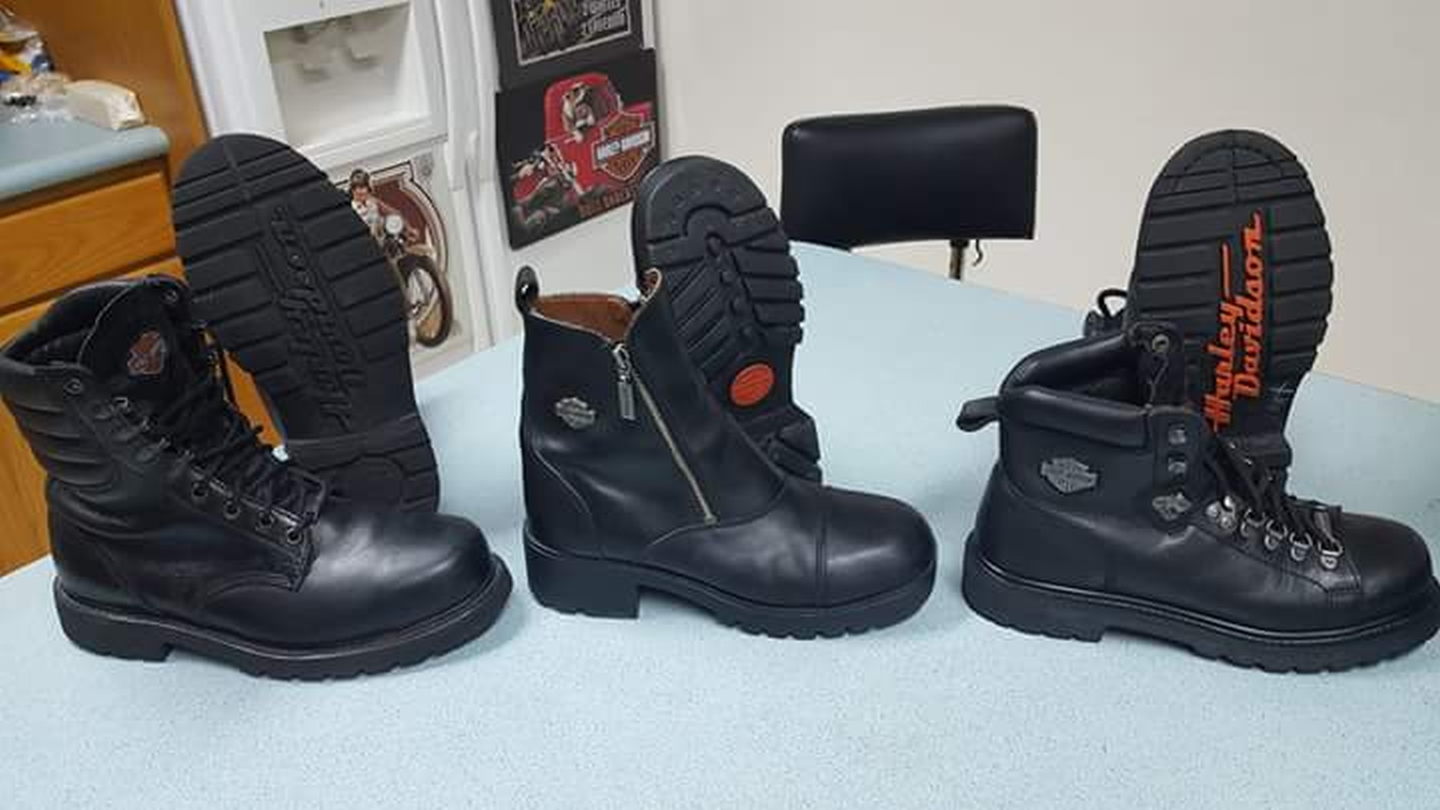 Three pairs of black leather boots pictures on a blue field. Of each pair the right boot is sitting normally while the left is propped against it's twin to show the tread. Two pairs on the ends are traditional lace-up engineer boots, the middle zip-up street boots. Emblazoned on the underside of one pair in red is the brand name.