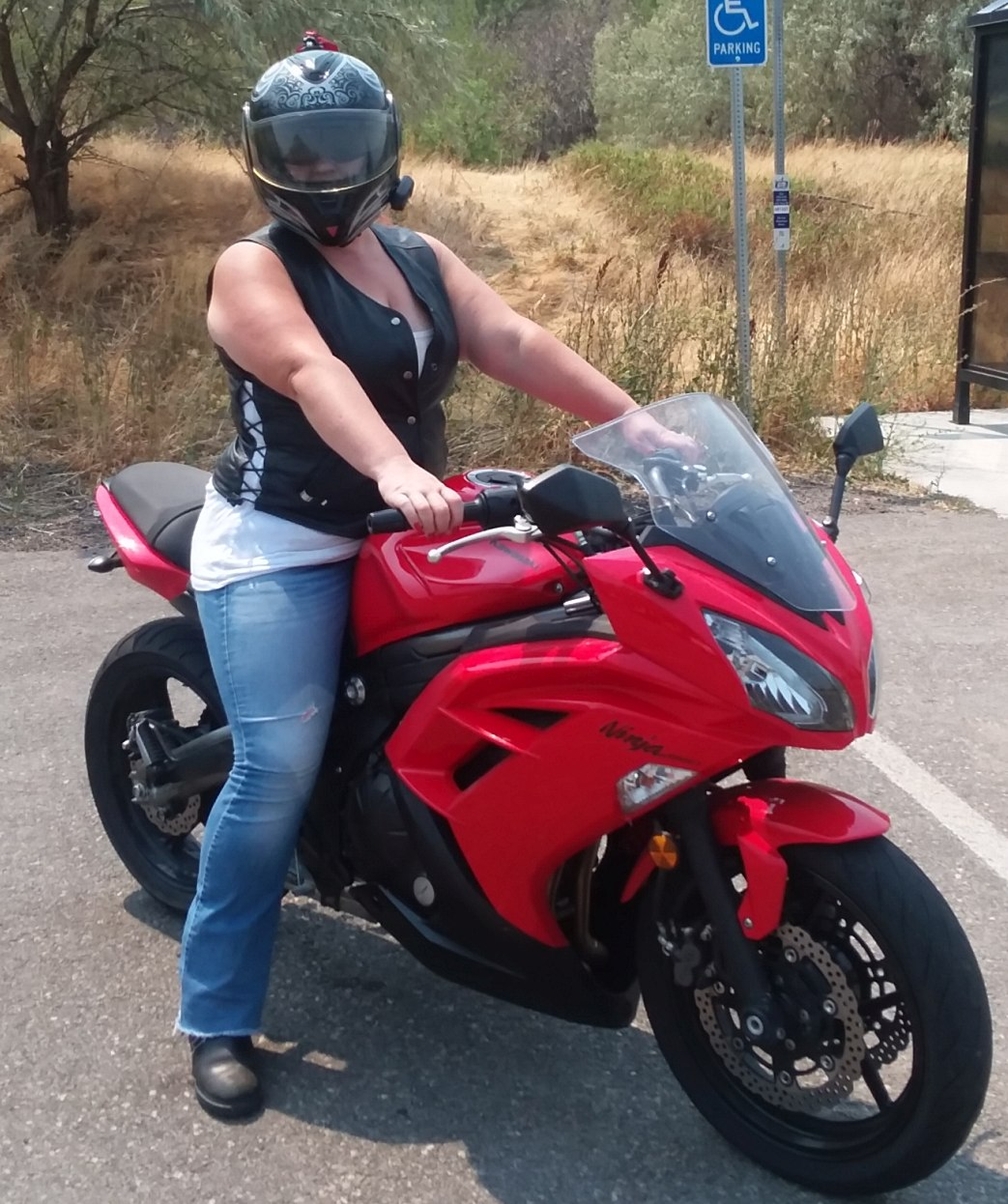 A helmeted woman sits astride a red Kawasaki Ninja 650. Her arms are extended to hold the controls of the bike, and her feet are planted firmly on the ground. She wears black boots, blue jeans, a white tank top and a black leather vest. The vest is partially unsnapped at the neckline to show the white top beneath. In the background, dry grass and scattered trees and a public bus stop.