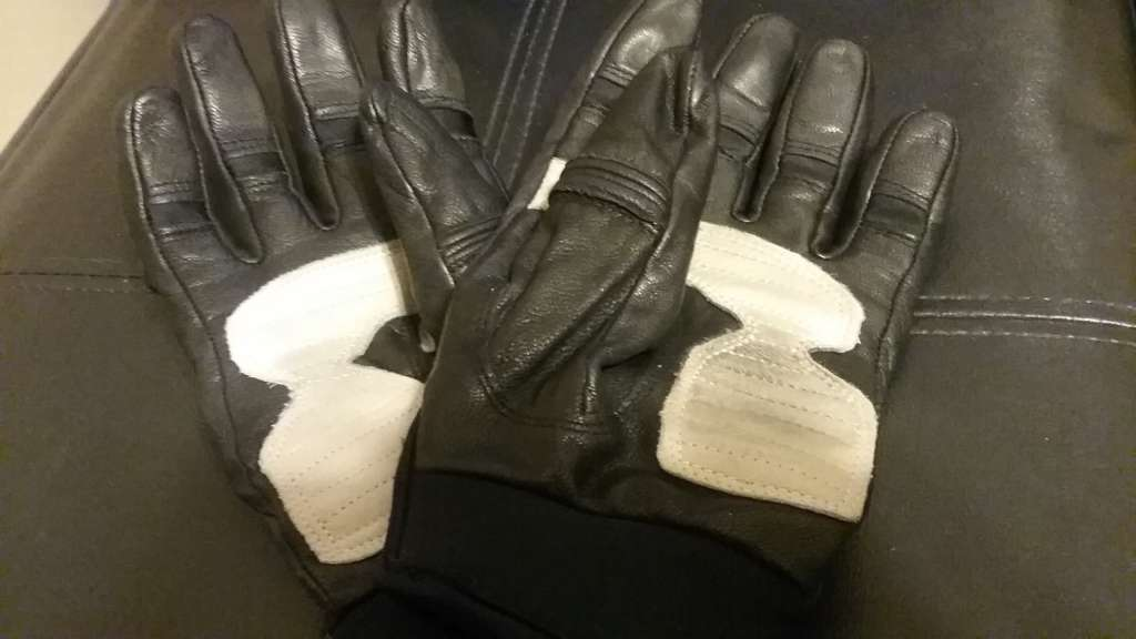 Indian Women's Review, A pair of sturdy looking black leather gloves lie palm side up, the palms are reinforced with a layer of white leather that are marked with minimal black scuff marks.