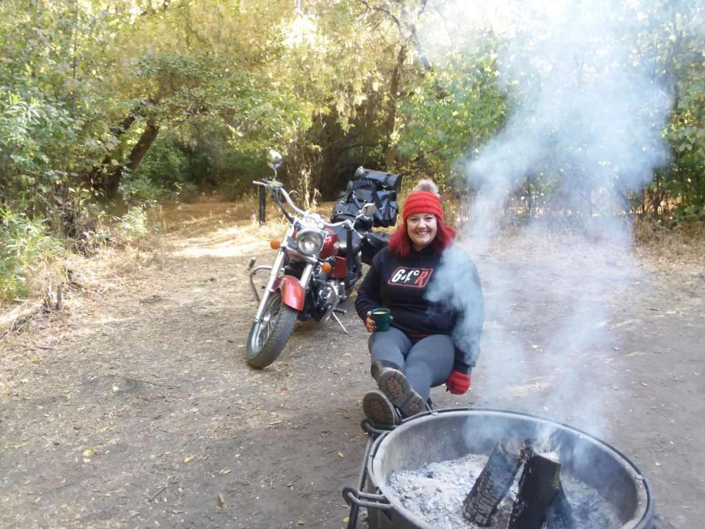 Indian Women's Review, A smiling woman holds a steaming cup of coffee, she sits with her feet up next to a smoking campfire in the woods. She is wearing a black hoodie with the 64 degree racing logo and a red knit hat and fingerless gloves. Her shiny red motorcycle is sitting behind her stacked with an assortment of black leather motorcycle luggage.