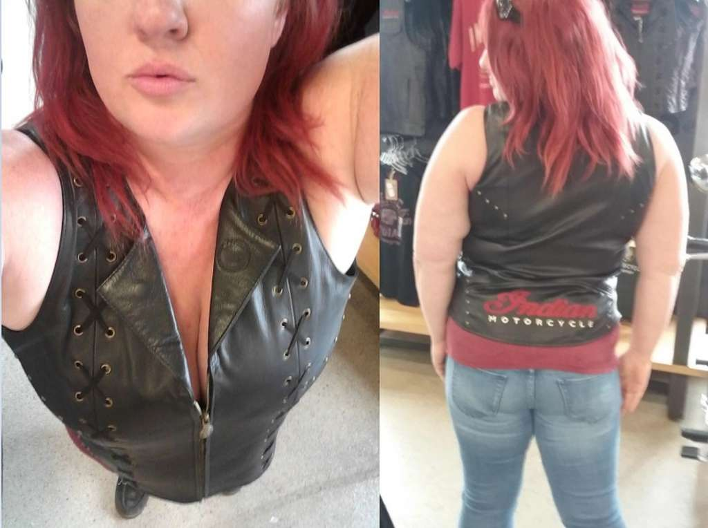 Indian Women's Review, A woman with red hair is at a dealership modeling a black leather motorcycle vest embroidered with the logo 'Indian Motorcycle'.