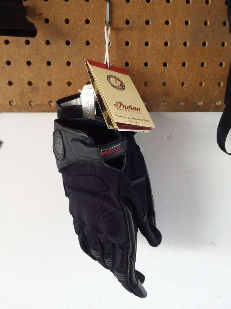A pair of Passage Gloves hang from a sheet of pegboard, the original label still affixed to the cuffs.