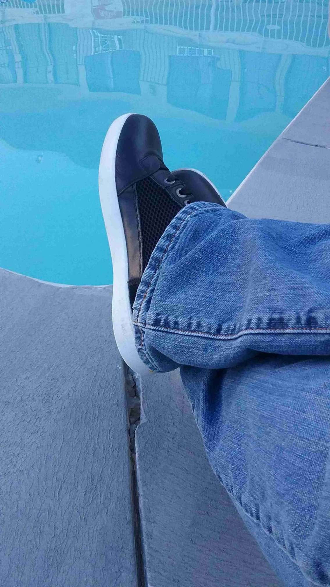 A man's feet, crossed at the ankles, is shown in the foreground. He's wearing the Mesh Hi-Top Sneakers from Indian Motorcycle, and they appear comfortable and relaxed. In front of him is the corner of a motel pool, the water inviting and blue.