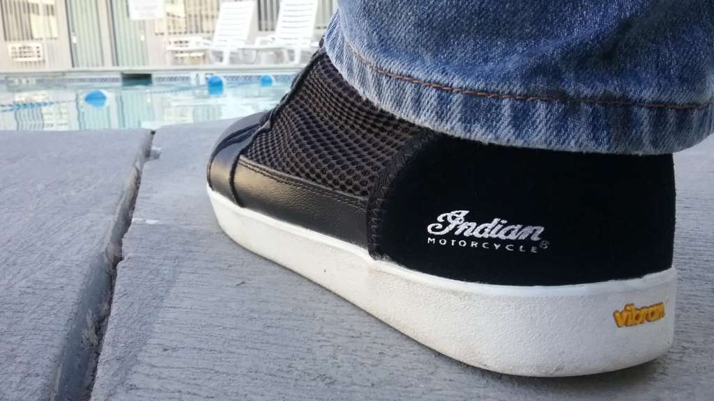 An extreme closeup of a Mesh Hi-Top Sneaker from Indian Motorcycle, showing the logo on the heel and the bright white sole stretching away. The mesh panel is clearly visible as well. In the background, a motel pool with desk chairs is vaguely visible.