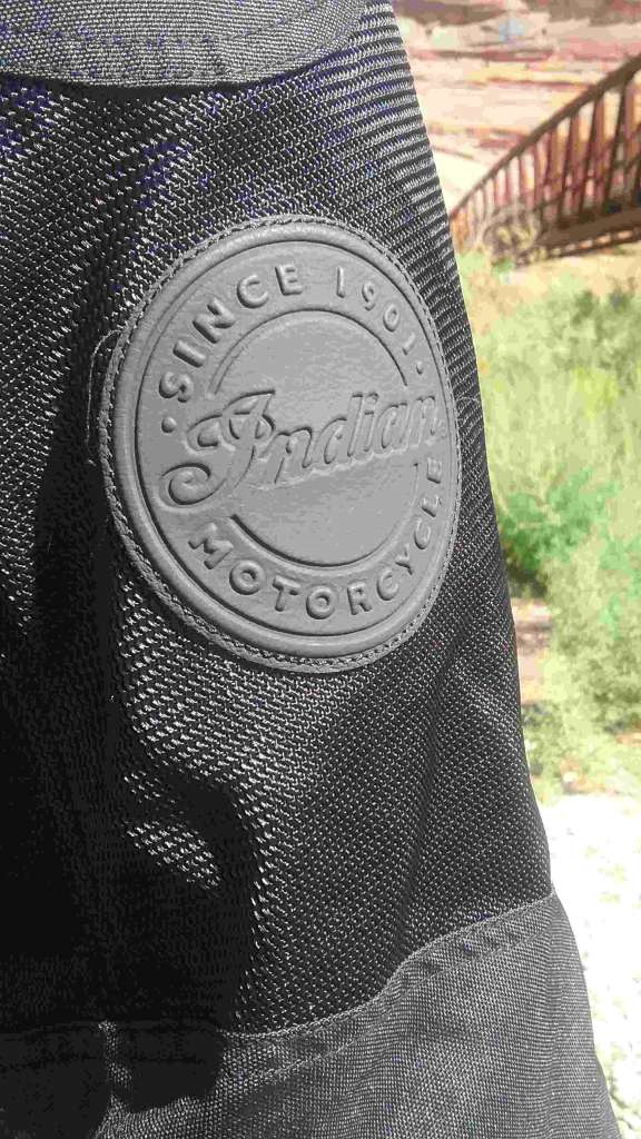 Displayed prominently in the foreground is the Indian Logo, embossed on a round patch of leather.