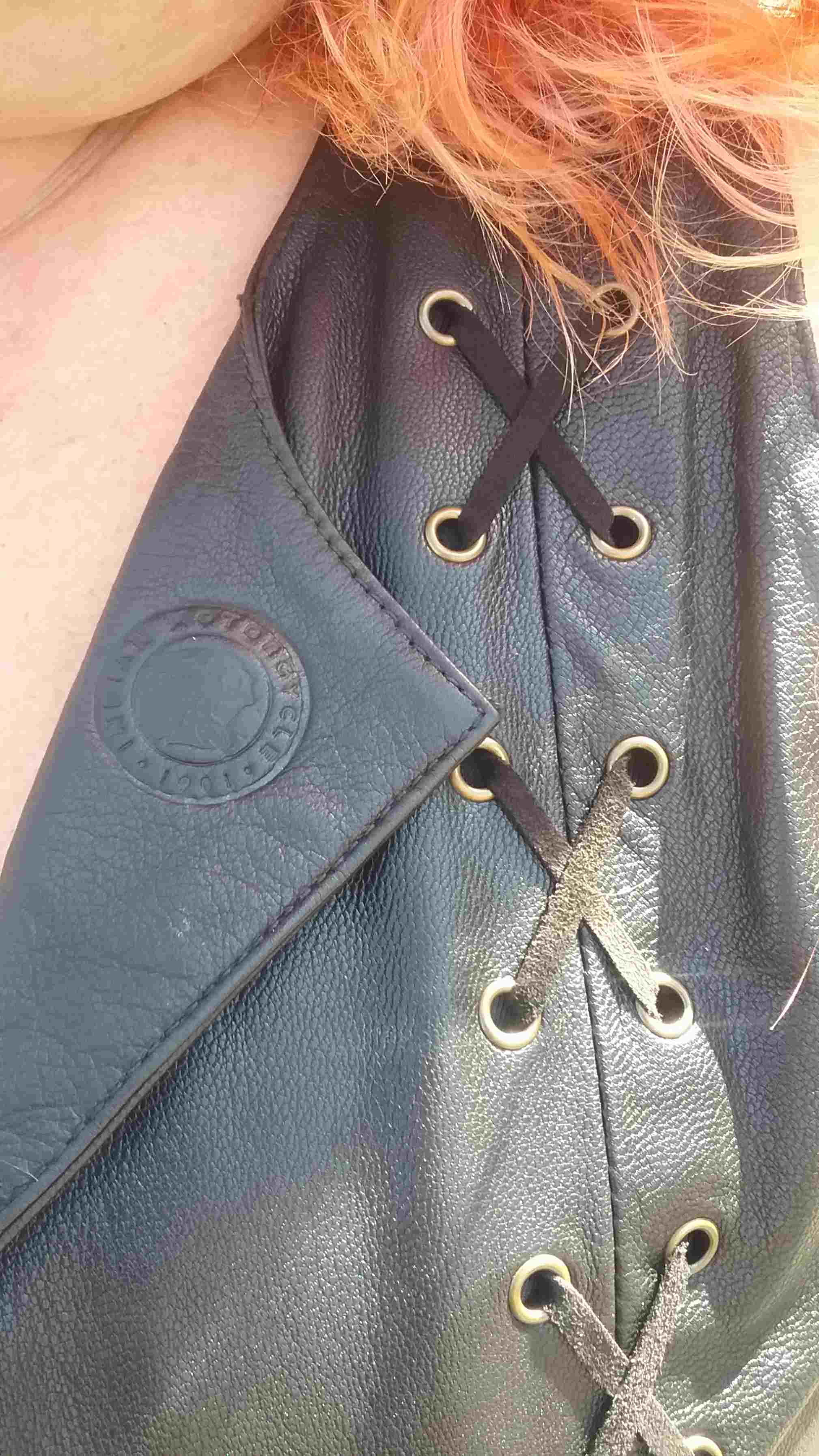 Indian Women's Review, A close up view of criss crossed black leather lacing through antiqued brass eyelets on a leather motorcycle vest, the vest shows a stamped Indian Motorcycle Logo on a trendy leather collar, the woman's red hair flows over the shoulders of the vest.