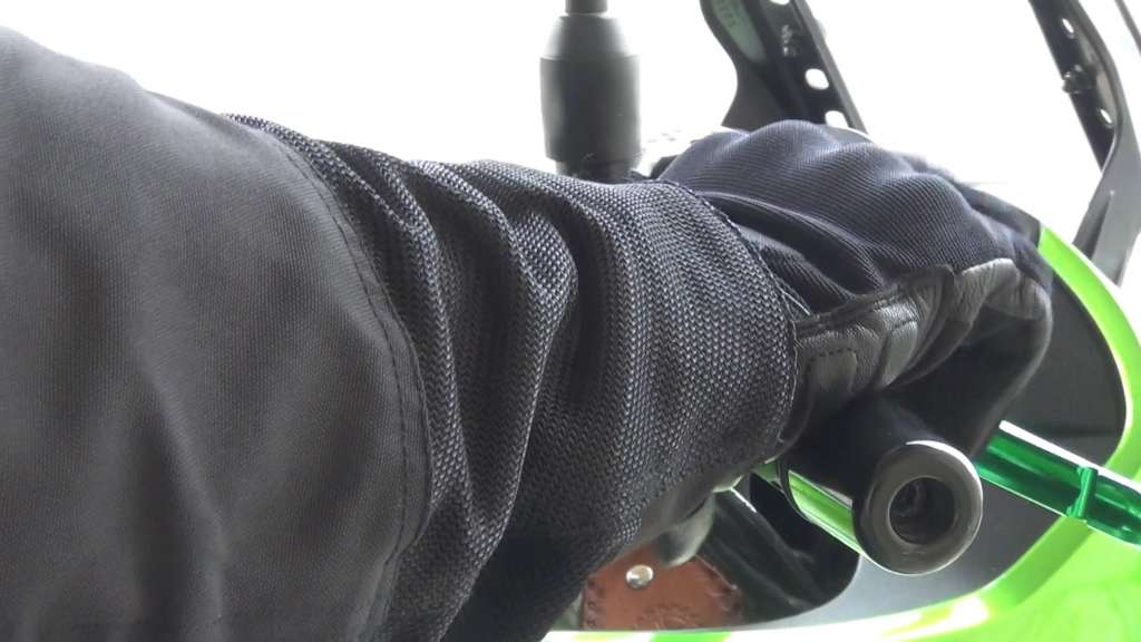 In extreme close-up, the Passage Gloves are wrapped firmly around the controls of a bike.