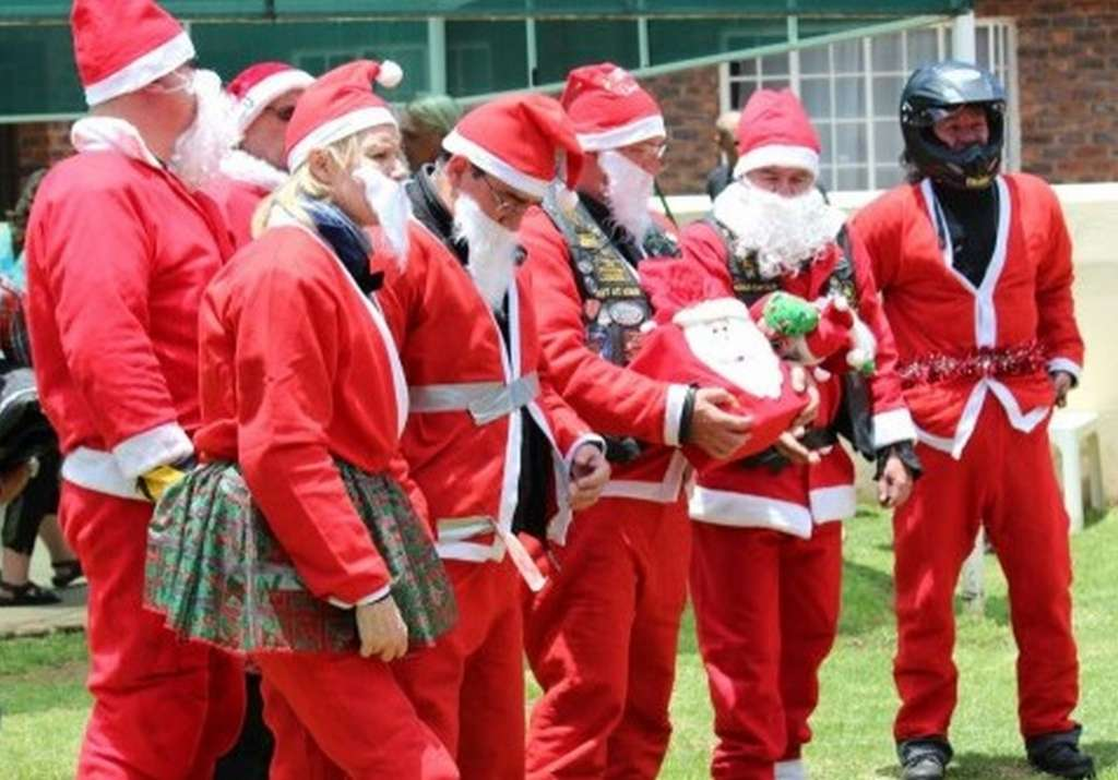 7 men dressed in Santa suits and beards. Several are holding gifts. One santa has his coat duct taped shut and one Santa has a tinsel belt and is wearing a motorcycle helmet!