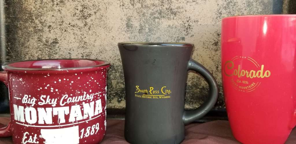 Souvenir coffee mugs displayed in natural light. Montana, South Pass City, Colorado.