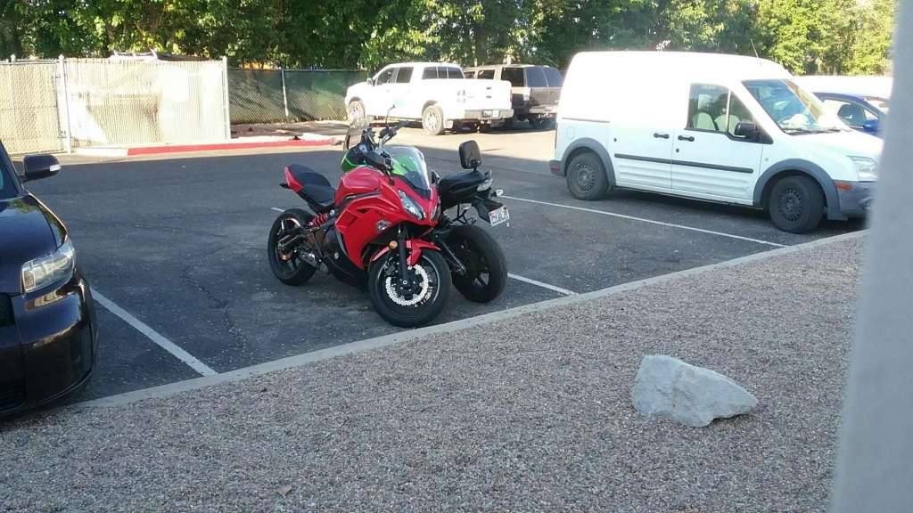 A Kawasaki Ninja 650R and Kawasaki Versys 650 are pictured, parked in a motel lot. They are arranged head to toe with each other, extremely close together.