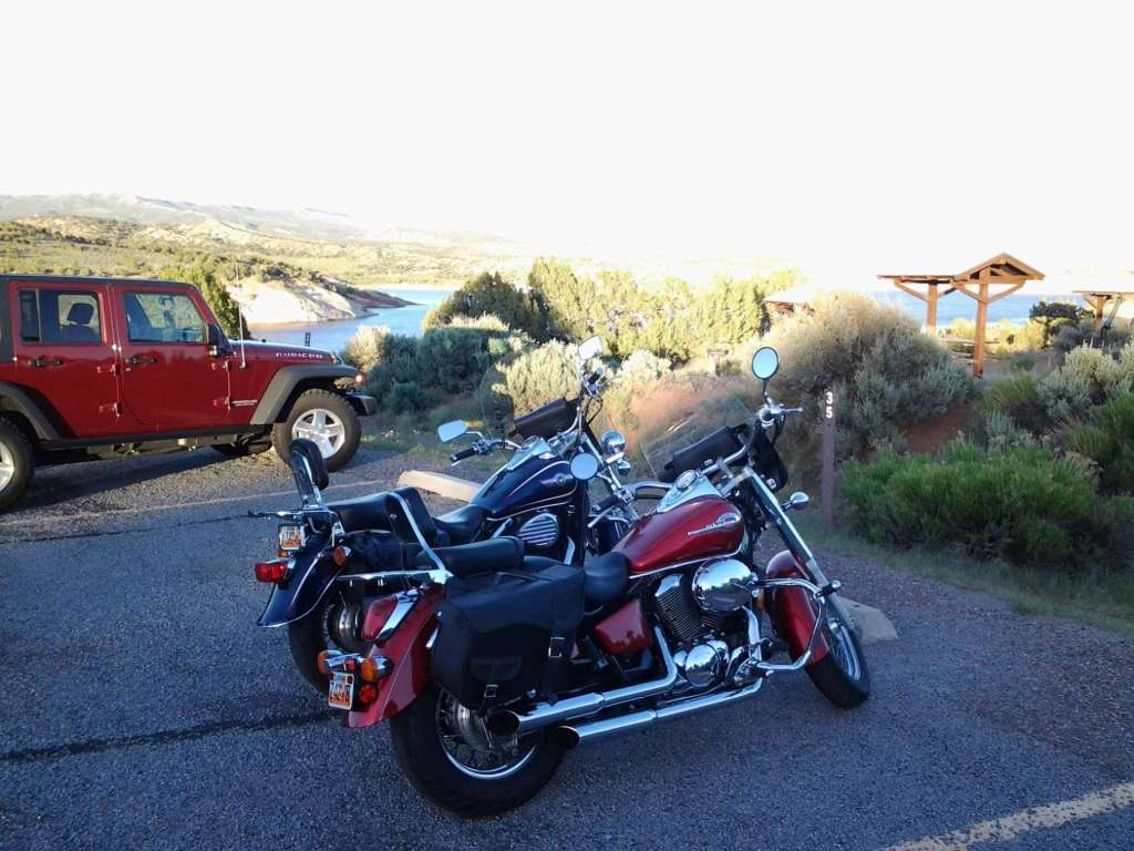 Red Honda Shadow ACE and blue Kawasaki Vulcan parked next to a campsite and large reservoir.