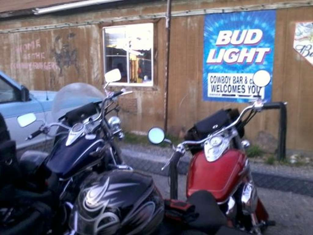 Red Honda Shadow and blue Kawasaki Vulcan parked outside a weathered clapboard tavern. The image is grainy and out of focus.
