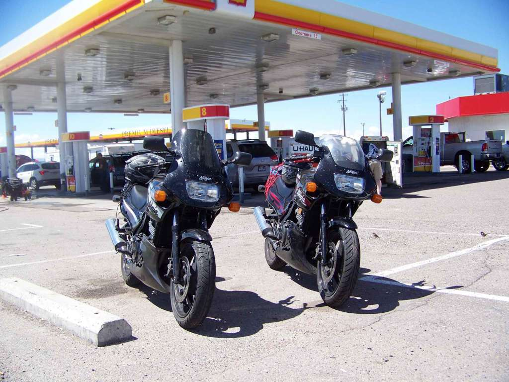 Two identical Kawasaki Ninja 500EX's parked on the apron at a large fuel plaza.