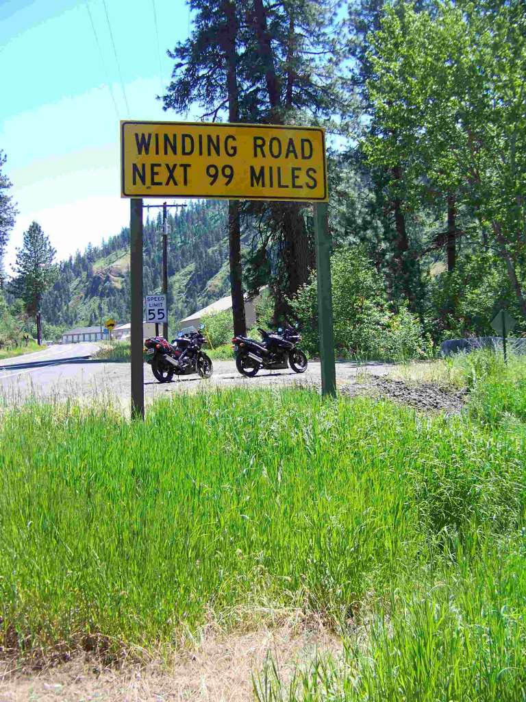 "Identical Kawasaki Ninja 500EX's are pictured on a gravel shoulder of a narrow mountain road. Prominent in the foreground, a signpost states ""WINDING ROAD NEXT 99 MILES""."