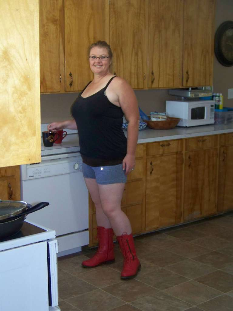 Staff writer Carrie Leaverton pictured in a rustic kitchen setting. She is wearing a casual black tank top, gray pajama shorts and bright red motorcycle boots.