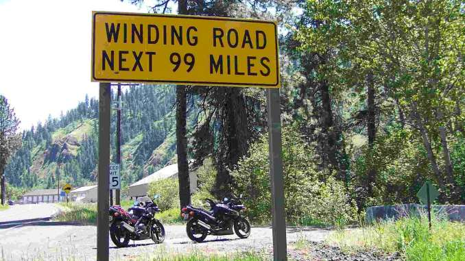 Two black sport motorcycles are parked in a forest near a yellow road sign that reads 'Winding Road Next 99 Miles'