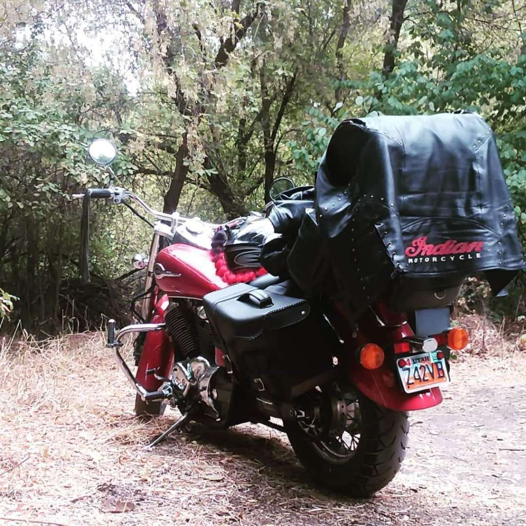 A shiny red and chrome Honda Shadow Motorcycle is parked in a clearing in the woods with black leather luggage packed onto the pillion and luggage rack.