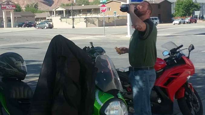 A man takes a large gulp of soda from a bottle with one hand, a gas station taquito in the other. He is standing between two Kawasaki Sport motorcycles in a 7-11 gas station parking lot. The barely visible background scenery includes beautiful red cliffs.