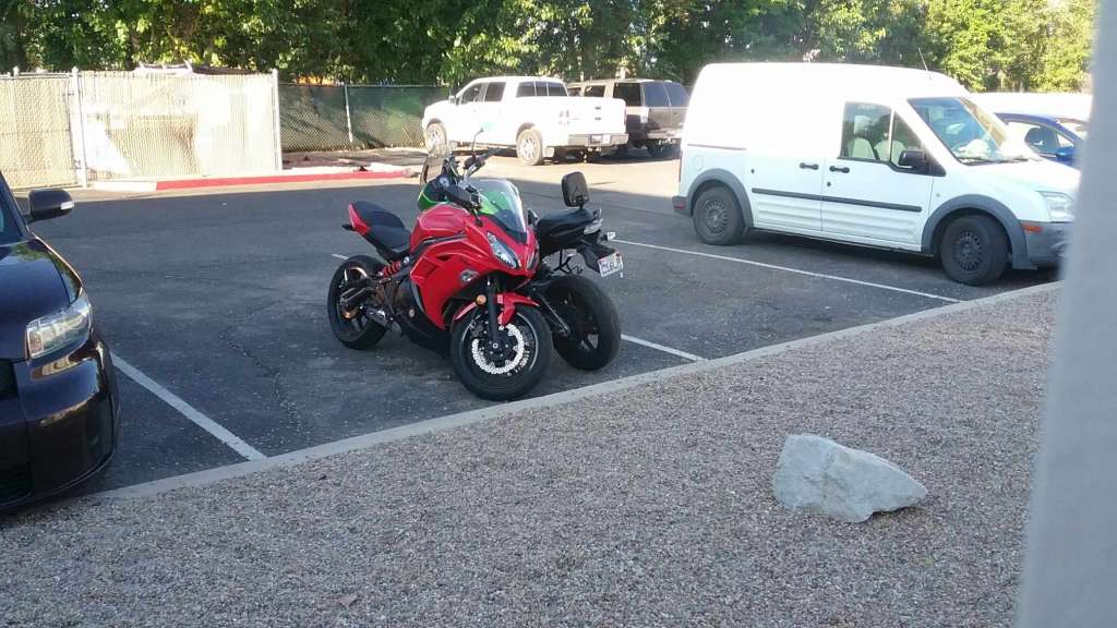 Two Kawasaki sport motorcycles are parked together, facing different directions with the handlebars turned towards each other, taking up minimal space in one parking spot.