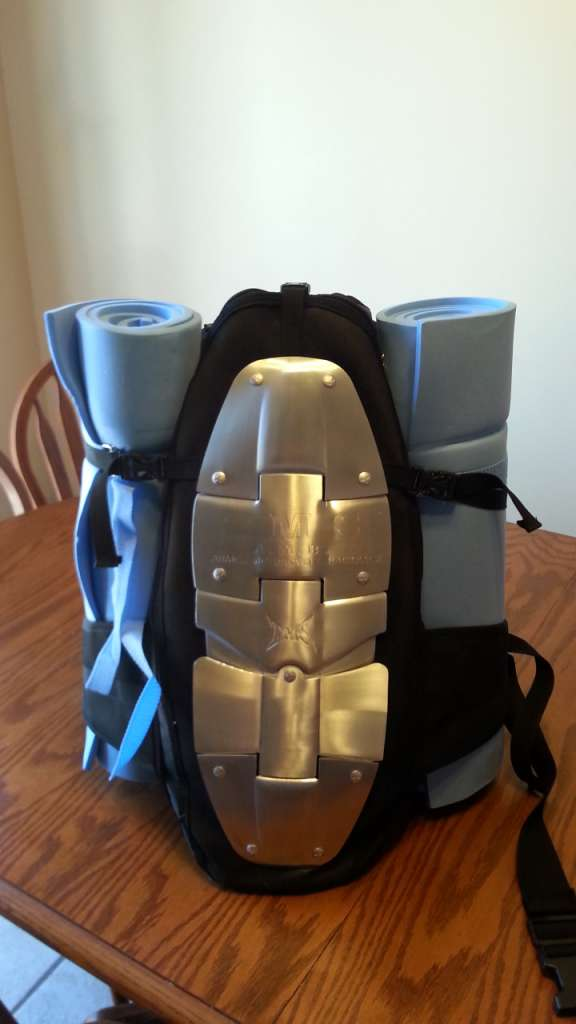 A backpack sits atop a table with 2 bedrolls strapped vertically on either side.
