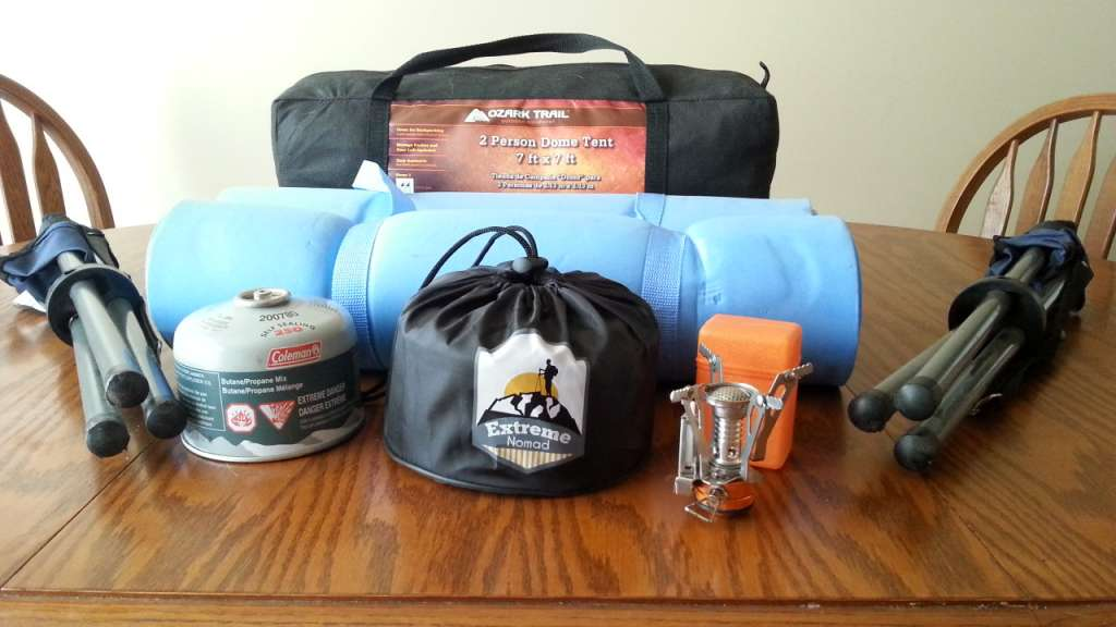 Various Camping Gear Including a compact dome tent, 2 bed rolls, 2 fold up tripod camp chairs, a butane fuel bottle, a travel size burner and a compact mess kit set atop a table.