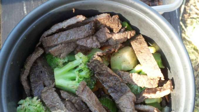 The mess kit crock is filled with bright green diced broccoli and mixed veggies with strips of sauteed steak.