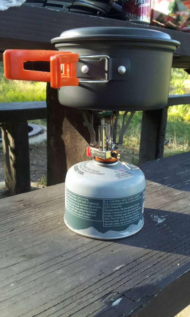 A Butane burner is placed atop a camp table with a mess kit pot heating on the burner.