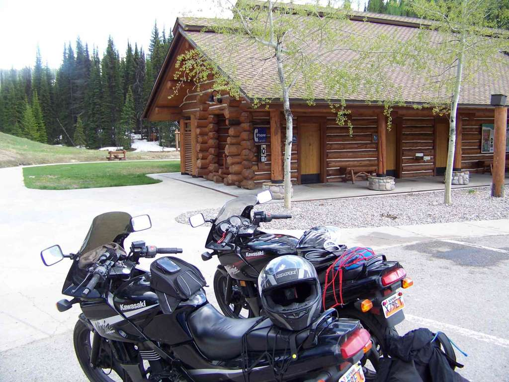 Two black sport motorcycles are parked near a log cabin club house in a forest with a little bit of snow under the trees. The parking lot is dry and the sun is out.