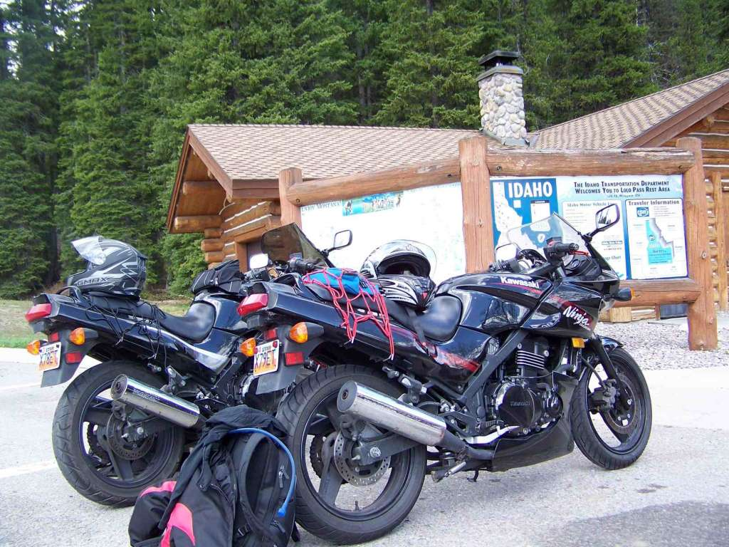 Two black sport motorcycles are parked together in a parking lot in a forest. The background shows an Idaho map and a Log Cabin Visitor's Center.