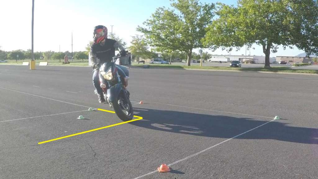 A rider leans into a right-hand turn with clear counterweighting posture, facing the camera. Yellow highlight lines describe the width of the turn, significantly shorter than the previous picture.