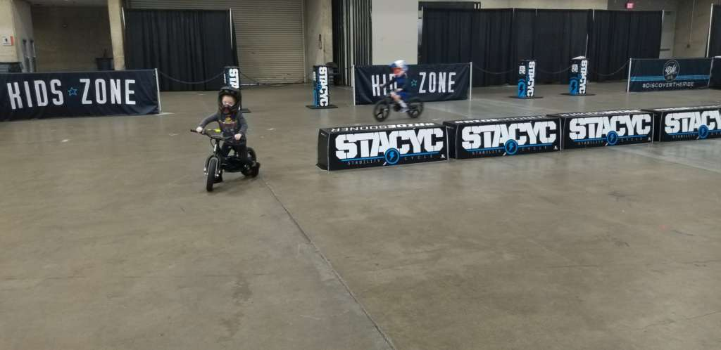 Young children in full motorcycle gear navigate a closed, padded oval track on STACYC Stability bikes.
