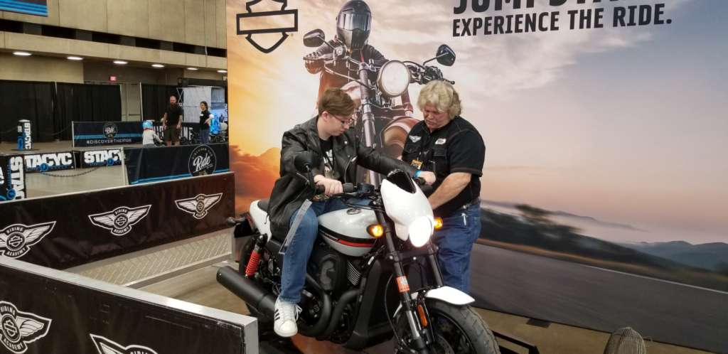 Our son sits on the Harley-Davidson StreetRod 750 while the handler instructs him in shifting techniques.