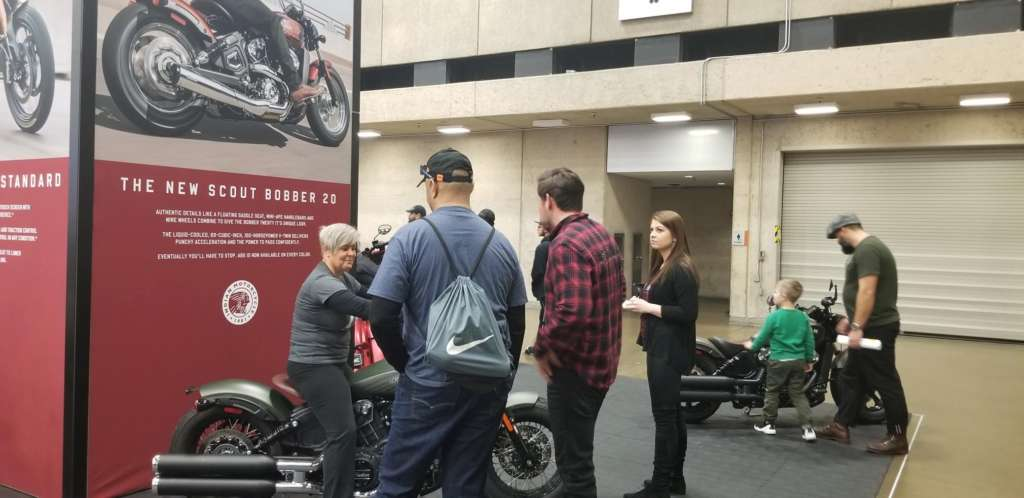 Several people mill around the Indian Scout Bobber display.