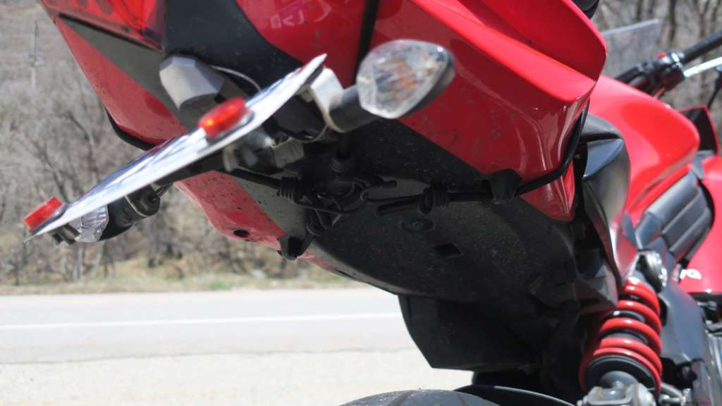A close up of the underside of a 2012 Kawasaki Ninja 650, with the Viking Sport Tail Bag mounted. Bungee cords criss-cross beneath the tail piece.