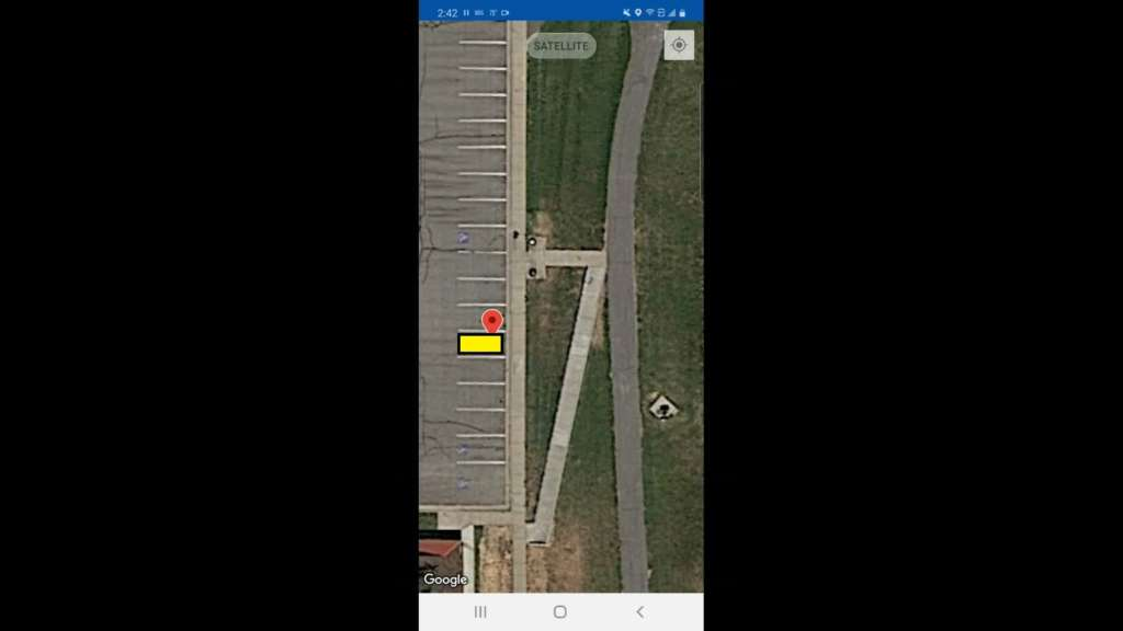 "Pictured is a screen grab from the Monimoto app, showing a GPS tag in Google Maps ""satellite"" view. The parking stall at the tag location is highlighted in yellow."