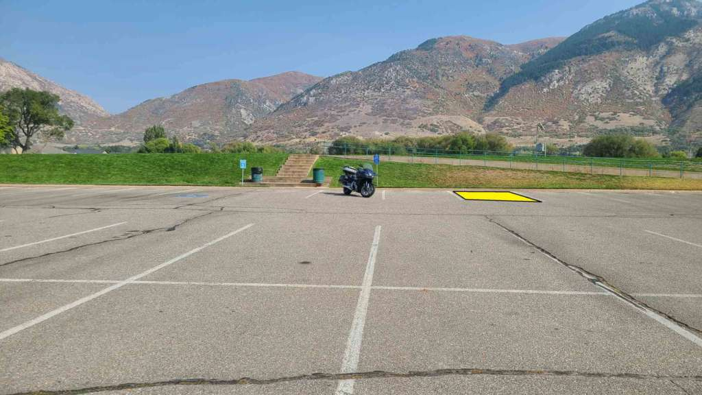 A parking lot is pictured with dramatic mountains in the background. Centered is a Honda CTX 1300. The second parking stall to the right is highlighted in yellow.