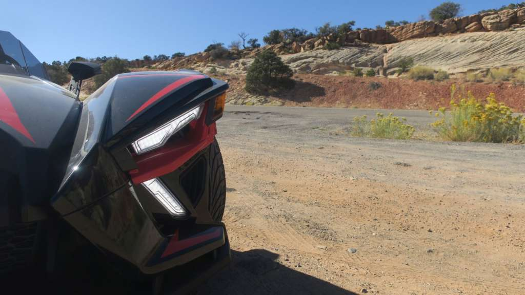 From TMW's Slingshot R review, a close-in angle of the Slingshots aggressive front end. Highlighted is the bright LED accent lights and rugged Utah scenery.