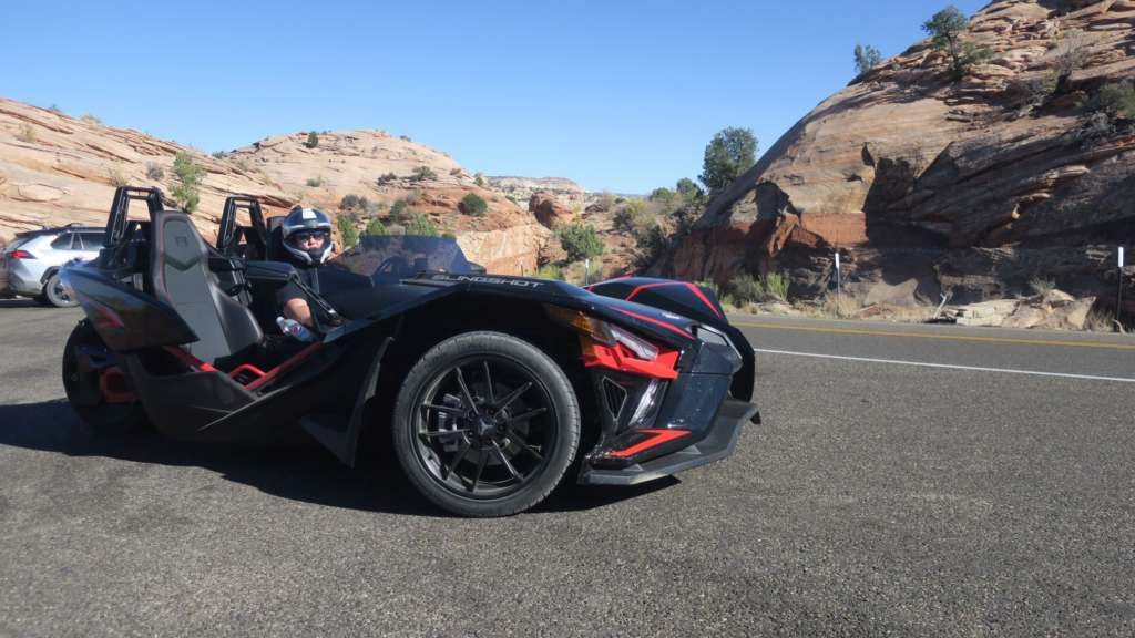 From TMW's Slingshot R review series, the Slingshot R sits imposingly in a roadside pullout, picturesque rock formations in the background.