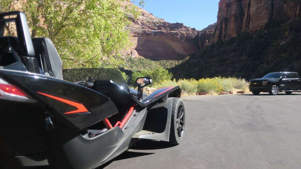 The passenger side of the Slingshot R from a low angle. In the background, immense rock formations from Utah's Zions National Park.