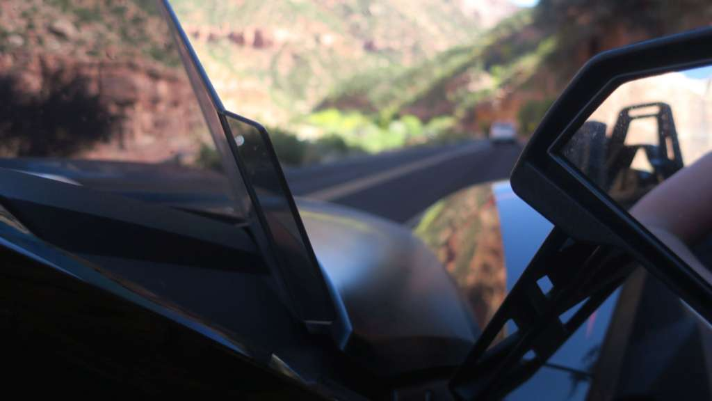 A tight angle shot from between the windshield and rearview mirror of the Slinghsot R. In the background, a blurred canyon road with rugged scenery.